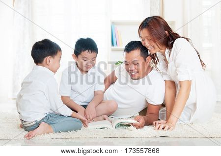 Beautiful Asian family enjoy reading at home