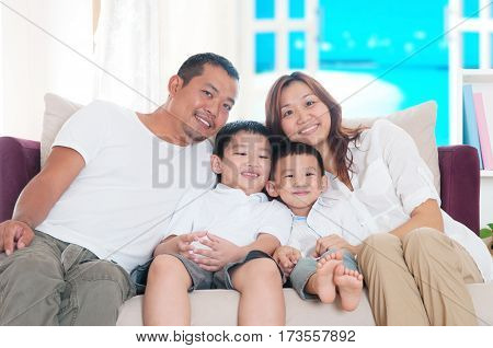 Indoor portrait of beautiful asian family sitting on sofa