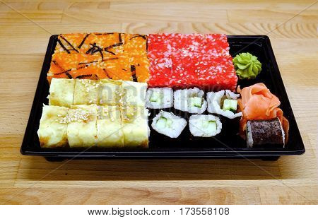 Sushi pieces on dark square tray on brown wooden table front view closeup