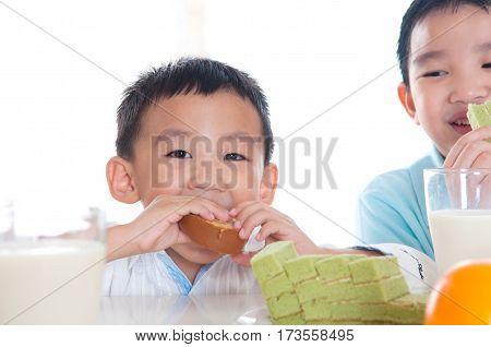 Lovely asian kids having breakfast at home