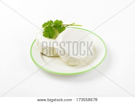 Wheels of soft ripened cheese with white mold rind