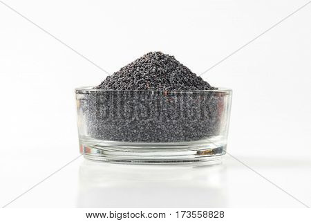Whole black poppy seeds in glass bowl