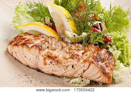 Grilled salmon fillet with fresh salad on the plate.