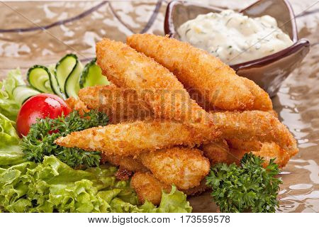 Pieces of fish fried in batter garnished with vegetables.