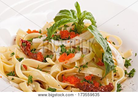 Close up of pasta with caviar decorated with leaf of basil isolated on a white background.