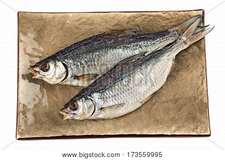 Dried salted bream fish on the brown plate.