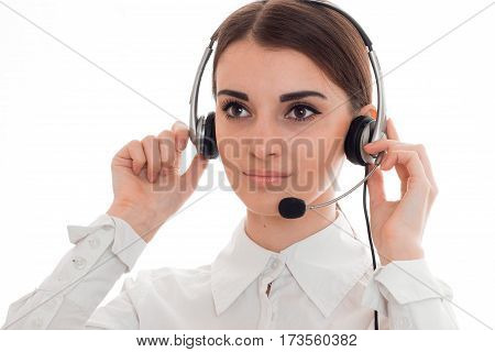 Portrait of a young beautiful girl that keeps hands dressed to head headphones with microphone closeup isolated on white background