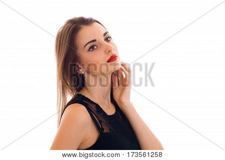 attractive young girl in black clothes is worth turning sideways and keeps a hand near the face isolated on white background