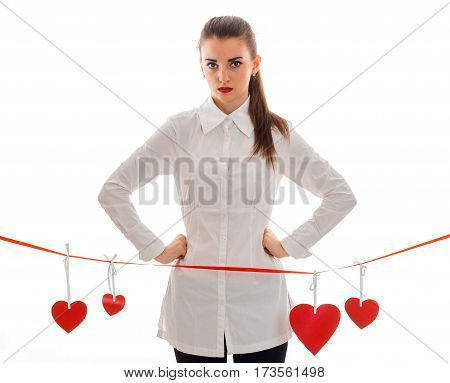 serious young girl in white shirt keeps your hands on the sides and stands near a Red Ribbon with hearts isolated on white background