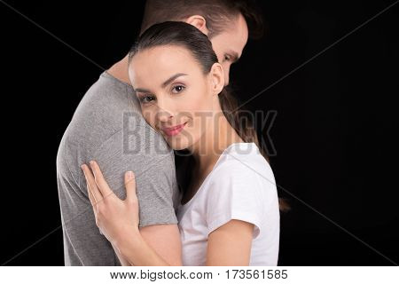 portrait of smiling woman bonding to man and looking to camera on black