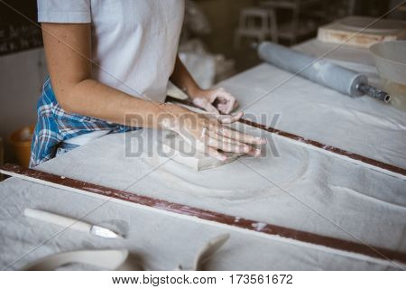 Sculptor prepares grey raw clay for modeling ceramic plate on big table with industrial fabric in workshop