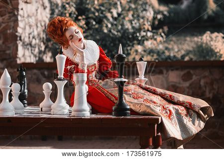The Red Queen is playing chess. Red-haired woman in a chic vintage dress. Fashion Photo of queen