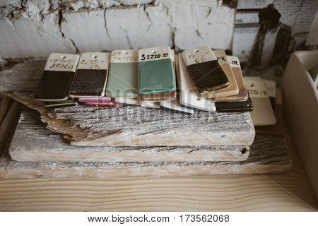 Colored glazed ceramic samples on old wood in workroom