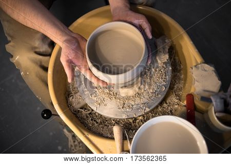 Hands of artist hold earthenware above pottery wheel