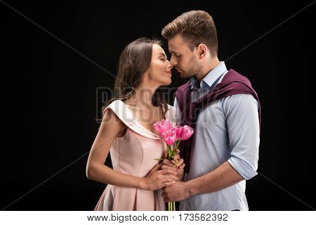 portrait of bonding couple in love with tulips bouquet in hands on black international womens day concept