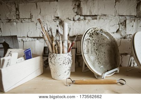 Pottery tools with wooden holders in ceramic vase and ceramic plate on shelf in pottery studio