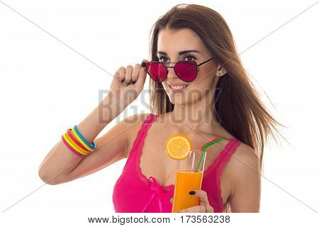 young sexy girl in sunglasses looks to the side and holding a glass of juice close-up isolated on white background