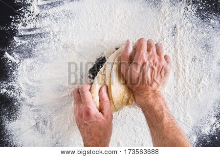 Baking concept. Flour, milk, butter, yeast and eggs carton on rustic wooden table, cooking ingredients. Unrecognizable man's hands top view knead dough on black background. Male baker