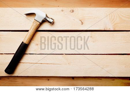 Wood background with a hammer home improvement concept