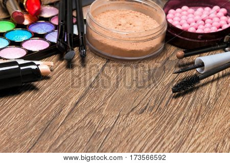 Frame of basic make-up products. Concealer, bottle of foundation, powder, blush, eyeliner, mascara, colored eyeshadow, lipstick and make up brushes with copy space