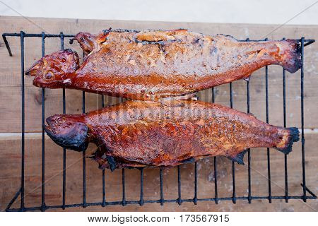 Trouts on charcoal bbq grillwhole baked trout grilled on wooden old boards.healthy eating concept. view from above.