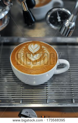 Coffee Cup With Latte Art On The Espresso Machine Tray