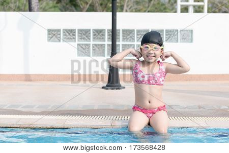 cute asian girl show muscle in swimming pool concept sport and vacation