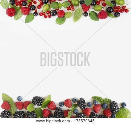 Various fresh summer berries isolated on white background. Ripe blueberry raspberry currant and blackberries with basil leaves. Berries at border of image with copy space for text. Top view.