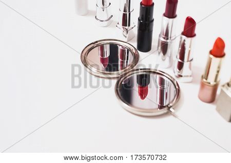 Multi-colored lipstick on white background. Reflection of lipstick in the mirror. Composition with makeup and a mirror. View from above. Concept. Decorative cosmetics flat lay