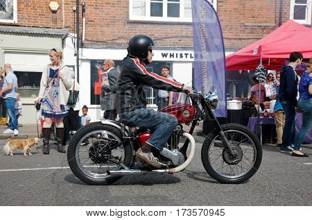 AMERSHAM, UK - SEPTEMBER 13: A vintage Ariel motorcycle is slowly driven down the centre of the road at the Amersham Heritage Day festival on September 13, 2015 in Amersham.