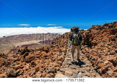 tourist man with backpack walking around the top of the volcano Teide in Tenerife Canary Islands Spain