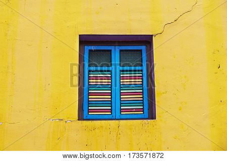 bright colors painted shutters window on yellow building wall