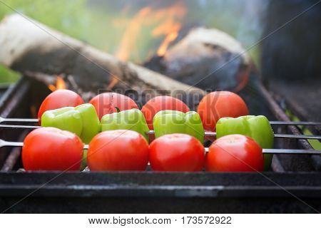 Grilling tomatoes and paprika on skewers with fire outdoors. Selective focus on paprika.