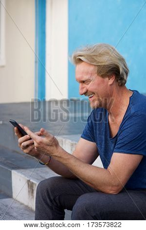 Happy Middle Aged Man Sitting On Steps Using Mobile Phone