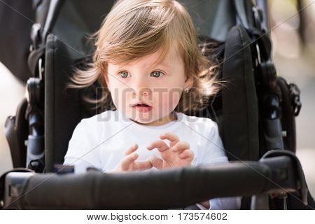 little and very beautiful baby girl sitting in the pram and waiting for mom