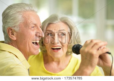 Portrait of a excited senior couple singing in microphone