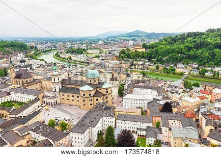 Panoramic view over stadt salzburg with salzach river, rainy day, fog and mountains, austria