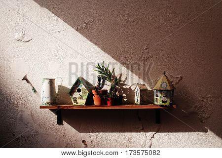 Garden objects on a shelf with afternoon sun coming from the side