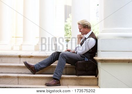 Man Sitting Outdoors On Steps And Working On Laptop