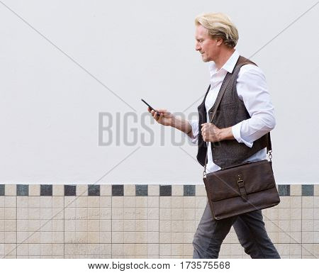 Man Walking Outdoors And Looking At Mobile Phone