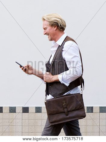 Happy Man Walking With Cell Phone And Bag