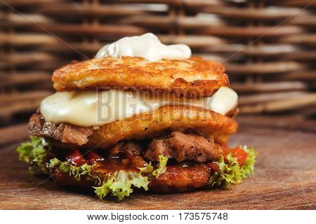 Delicious hamburger potato pancakes with meat lettuce cheese tomatoes on the wooden board.