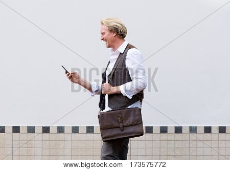 Happy Business Man Walking With Cell Phone And Bag.
