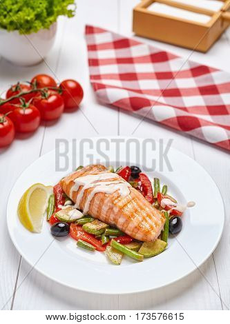 Salmon steak grilled with herbs and lemon, spicy white sauce and grilled vegetables on a white plate on a light wooden background. Close up.