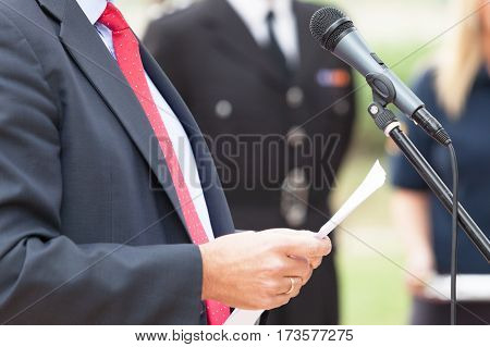 Politician is giving a speech. Speaker. Speech. Microphone. News conference.