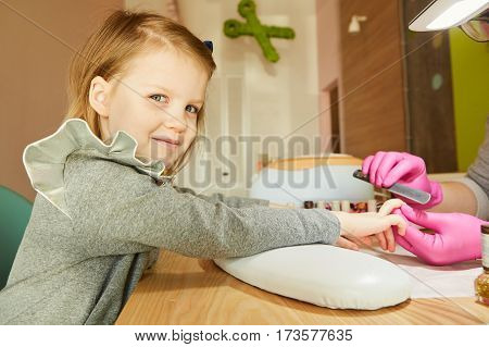 Little girl in nail salon receiving manicure by beautician. Little girl getting manicure at beauty salon