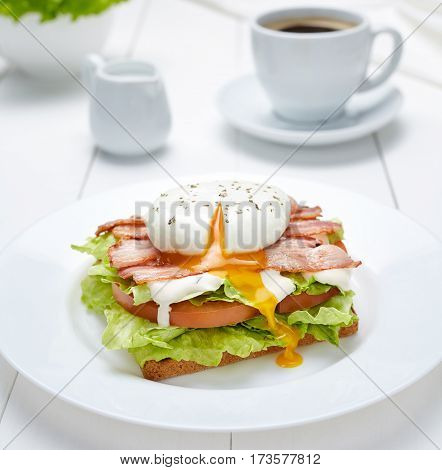 Low carb diet. Poached egg on bread with bran, lettuce, tomato and bacon on a white plate on a light background with a cup of coffee. A healthy breakfast.