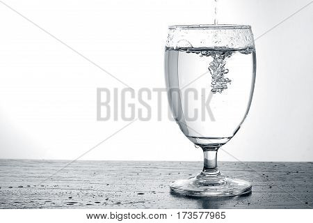 Pouring water into a glass on wooden table with copy space