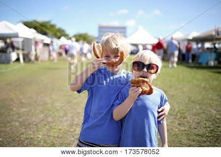 Two young boys: a seven year old and his little brother are having fun eating pretzles and making funny faces at a farmer's market outside in Marco Island Florida.