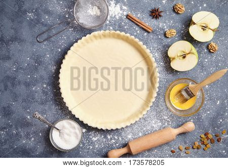 Dough preparation recipe pie, cake, tart, food flat lay on kitchen table background. Baking form and ingredients for apple pie. View from above.